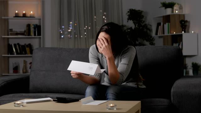 smutna kobieta narzekana czytając list w nocy - negacja filmów i materiałów b-roll