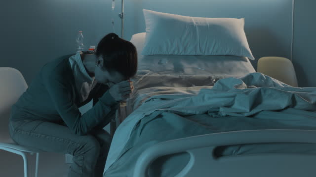 sad woman crying next to an empty hospital bed - morte video stock e b–roll