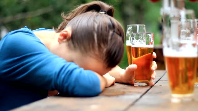 Sad woman drinking beer outdoors video
