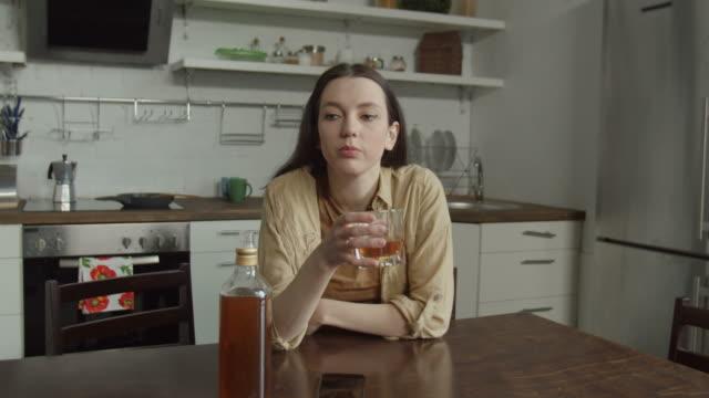 sad woman drinking suffering from cheating husband - samotność filmów i materiałów b-roll