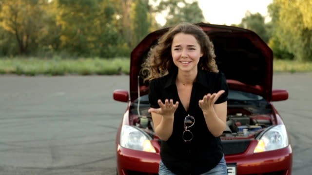 Sad woman in front of her broken car on the street video