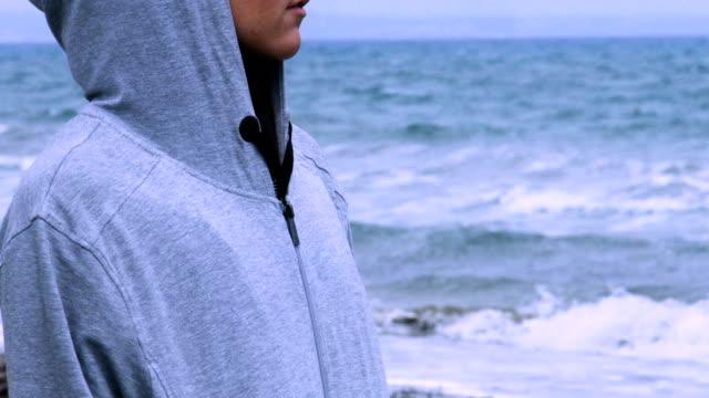 Sad woman in hoodie walking alone on empty beach, looking at horizon, depression