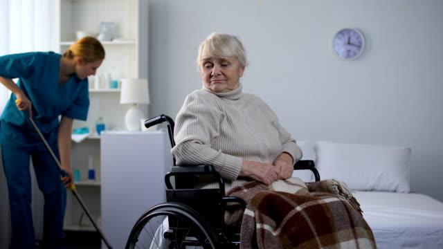 donna triste in sedia a rotelle che guarda la sala di pulizia del bidello dell'ospedale, centro medico - addetto alle pulizie video stock e b–roll