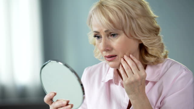 sad woman looking at face reflection and crying, unhappy with wrinkled skin - collagene video stock e b–roll