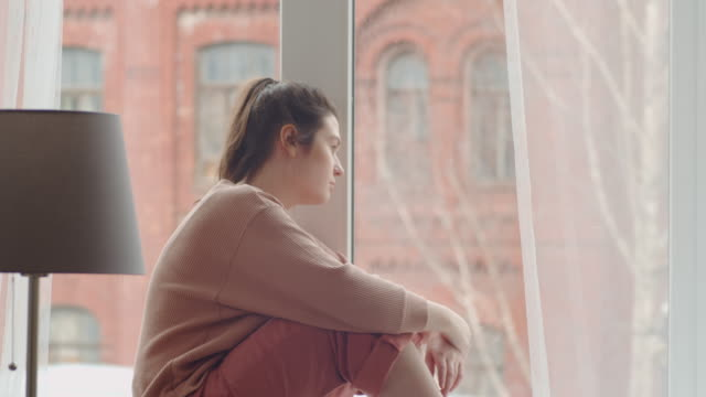 Sad Woman Looking through Window and Touching Glass with Fingers Young bored woman sitting on sill, looking through the window and touching glass with fingers while spending lockdown at home lockdown stock videos & royalty-free footage