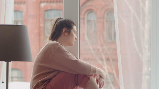 üzgün kadın pencereden bakıyor ve parmaklarla cama dokunuyor - tecrit stok videoları ve detay görüntü çekimi