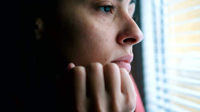 sad woman looking through window - stress emotivo video stock e b–roll