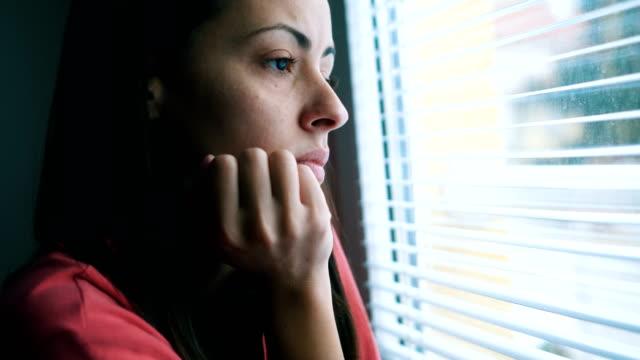 stockvideo's en b-roll-footage met treurige vrouw op zoek door raam - vrouw verdrietig