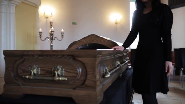 sorgliga kvinna sätta röda ros i kistan vid begravning video