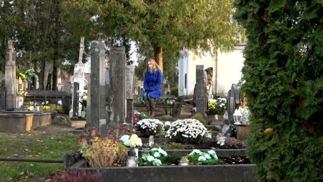 sad kvinna sitter på bänken nära graven av make far på kyrkogården. zooma ut. 4k - ljus på grav bildbanksvideor och videomaterial från bakom kulisserna