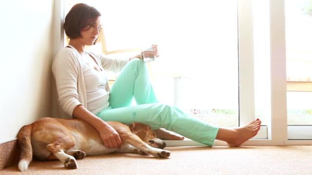 Sad woman siting on the floor near the friendly dog video