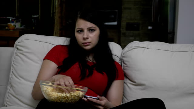 Sad woman sitting on the couch and eating popcorn video