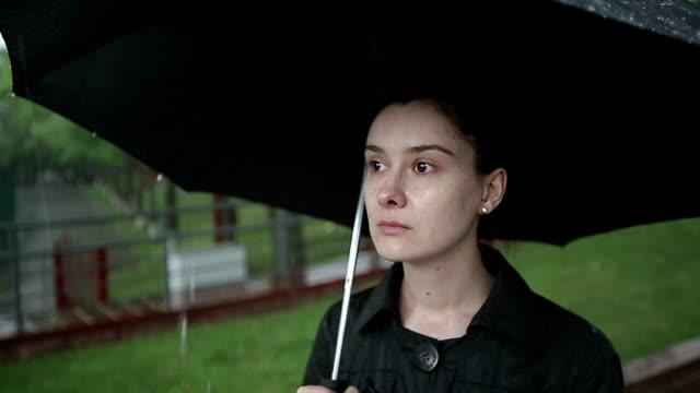 Sad woman standing on the street under heavy rain. video