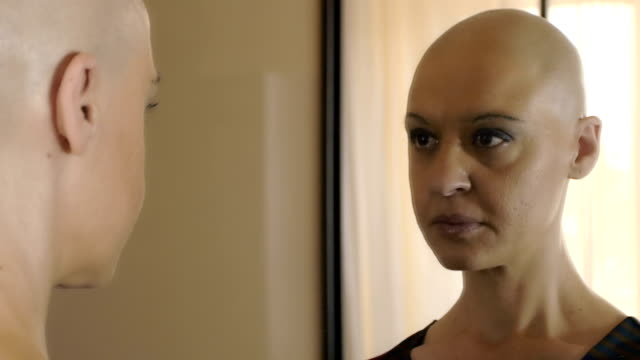 sad woman suffering from cancer at the mirror thinking: loneliness, fear Real bald cancer survivor woman looking calmly into the mirror cancer patient stock videos & royalty-free footage