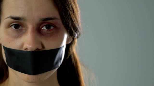 vídeos y material grabado en eventos de stock de mujer triste con la boca con cinta mostrando amarrados de manos, víctima indefensa de secuestro - human trafficking