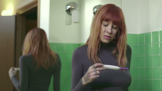 Traurig besorgt Mädchen Frau mit Schwangerschaftstest Kit wie zu Hause fühlen. – Video