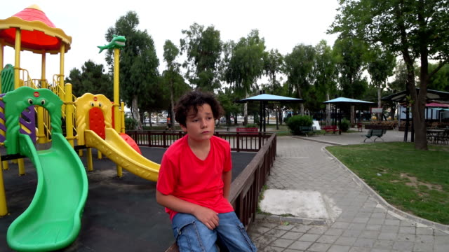 Sad young boy at the playground video