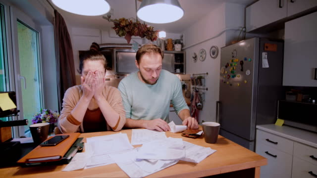 Sad young couple paying the bills. Man and woman sitting in the kitchen and sorting checks and accounts video
