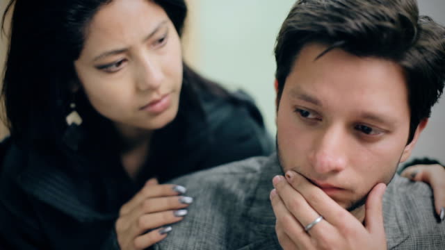 Sad young man consoled by a young woman. Indoor video of sad young man consoled by a young woman. Selective focus is on young man and young woman is defocused in the background, she is holding his shoulders from behind and supporting him. Two people, horizontal composition with selective focus. comfort stock videos & royalty-free footage