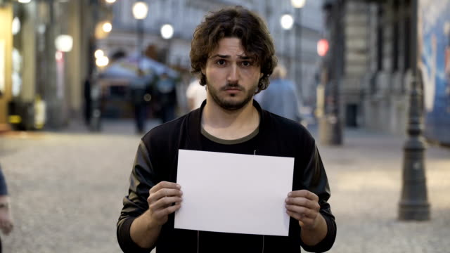 Sad young man holding a white copy space banner on the street video