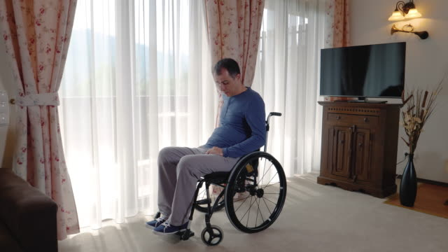 Sad young man in wheelchair looking through the window