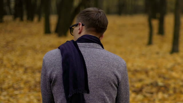 Sad young man sitting alone in gloomy autumn park, feeling unhappy and lonely video