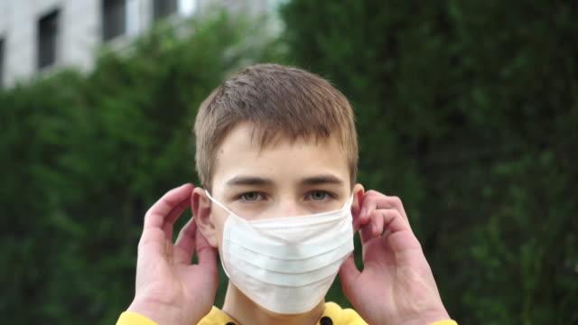 vidéos et rushes de adolescent triste de jeune homme met sur un masque bleu médical protecteur sur un fond de végétation verte. sweat-shirt jaune vif - enfant masque