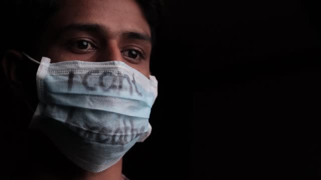 Sad Young man with wearing I Can't Breathe inscription on medical face mask with copy space. Concept of Protest about Human Right of Black People in U.S. America