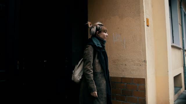 sad young woman going out from her apartment - odejście filmów i materiałów b-roll