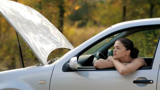 vídeos de stock e filmes b-roll de sad young woman in broken car - berma da estrada
