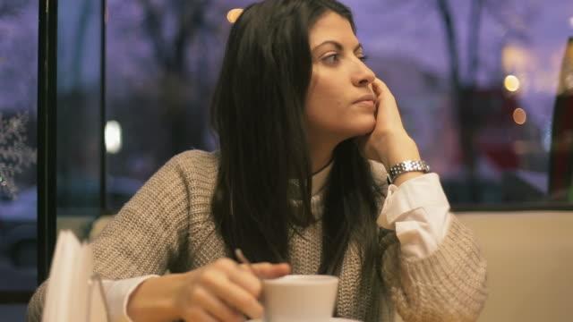 smutny młoda kobieta w kawiarni. - osamotnienie filmów i materiałów b-roll