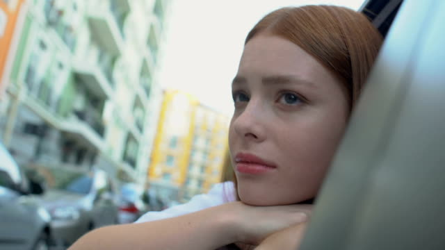 Sad young woman looking at city sitting taxi, relocation depression, nostalgia Sad young woman looking at city sitting taxi, relocation depression, nostalgia redhead stock videos & royalty-free footage