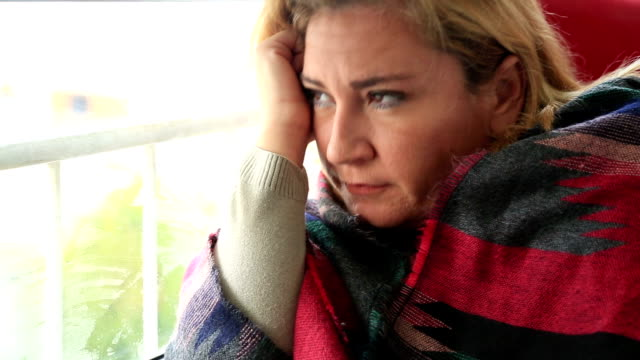 Sad young woman looking through window video