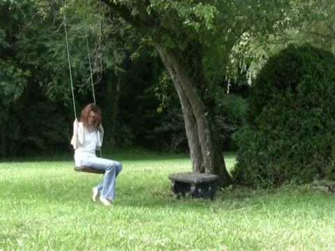 vídeos de stock e filmes b-roll de triste jovem sentado numa baloiço de corda pal - só mulheres jovens