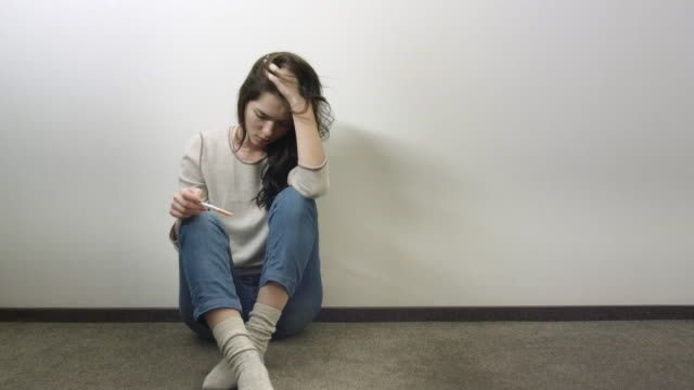 Sad young woman sitting on the floor with pregnancy test video