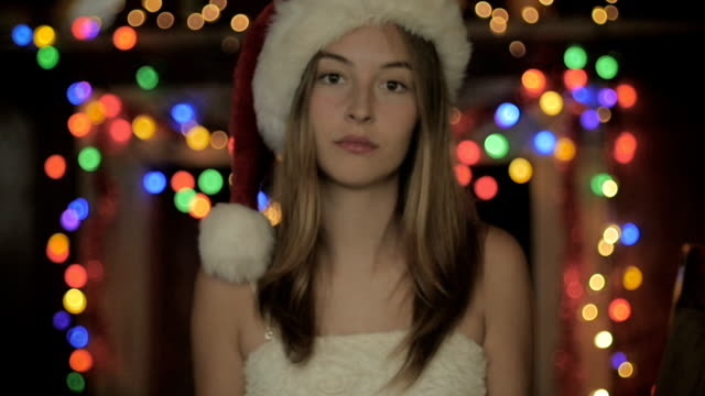 A sad young woman wearing a Christmas hat looking bored video