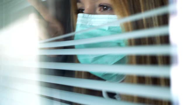 vídeos y material grabado en eventos de stock de triste joven usando máscara de protección médica mirando por la ventana - social media