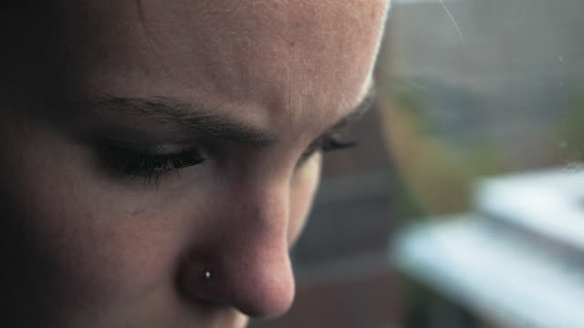 Sad Young Woman's Face in Extreme Closeup Sad young woman's face looking down and out a window. Profile. Extreme close up. extreme close up stock videos & royalty-free footage