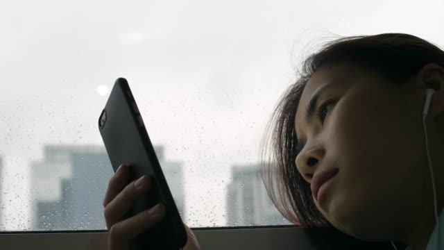 悲しみの女性が雨の日に音楽を聴く - 女性 落ち込む点の映像素材/bロール