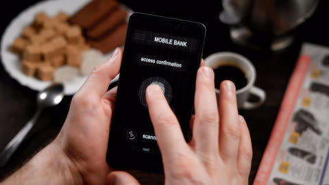 vidéos et rushes de accès sûr et rapide internet, mobile banking avec balayage du doigt. l'application sur le smartphone, l'homme s'applique son doigt au scanner, le programme permet d'accéder aux comptes - vue partielle