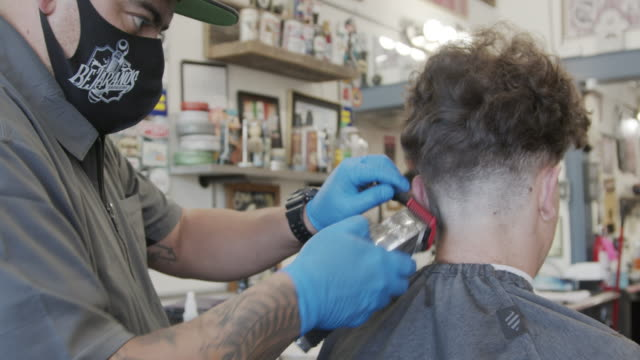Safely Visiting the Barbershop during COVID-19 Coronavirus Pandemic Professional Barber wearing a Protective Facemask gives a young man a haircut during COVID-19 Coronavirus Pandemic hairstyle stock videos & royalty-free footage