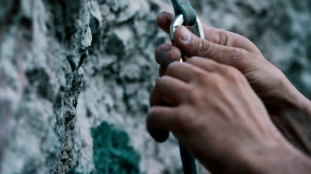Safeness for rock climbing Close up video of climber's hands removing the climbing rope from the carabiner on the rock. b roll stock videos & royalty-free footage