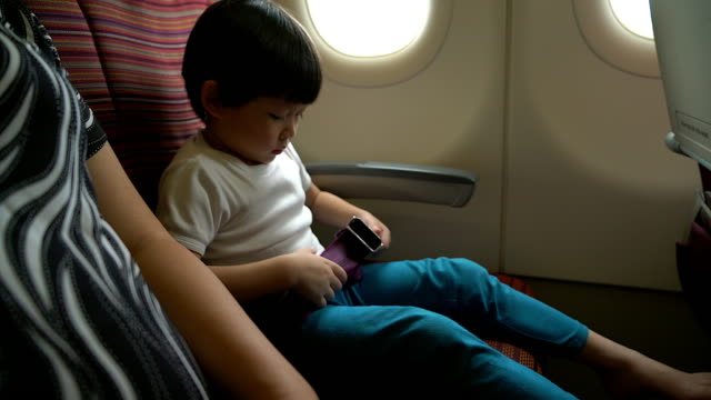 Safety concept young boy fasten seat belt at seat on airplane during flight travelling. video