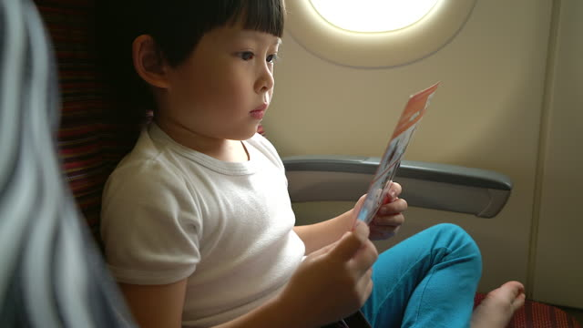 Safety concept young boy reading safety instruction on airplane during flight travelling. video