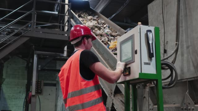 safety inspector having a look at a machine that controls the conveyor belt - odzyskiwanie i przetwarzanie surowców wtórnych filmów i materiałów b-roll
