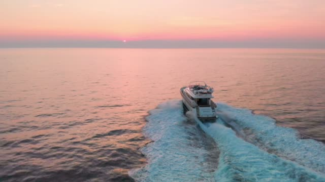 Sail away into the sunset Aerial view of a luxury yacht on the sea at sunset. Perfect unobstructed view over the horizon from this spot. Handsome man the owner of the yacht living the good life. yacht stock videos & royalty-free footage