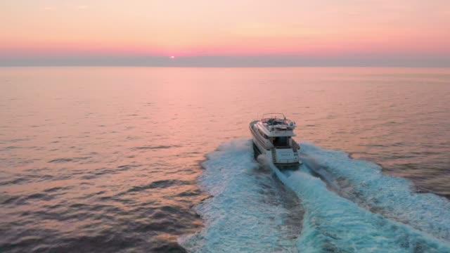 vídeos y material grabado en eventos de stock de navegar lejos en la puesta del sol - yacht