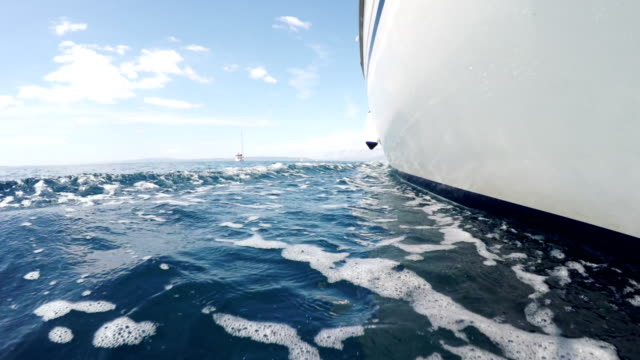 Sail boat low angle shot Sail boat following an other boat left side looking forward low angle just over sea surface shoot mast sailing stock videos & royalty-free footage