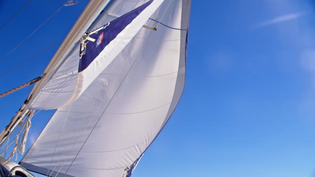 SLO MO Sail in the wind Slow motion low angle shot of a jib sail on a sailing boat with a clear sky in the background. Adriatic Sea. Croatia. yachting stock videos & royalty-free footage