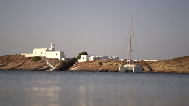 Sailboat anchored before coastal, white church Group of middle-aged friends explore Greek islands by sailboat. greek islands stock videos & royalty-free footage